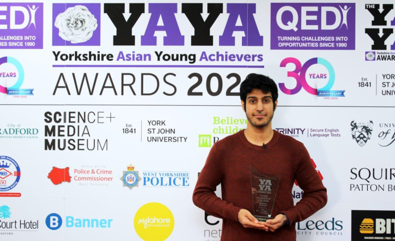 A young man holding a perspex award in front of a sponsorship backdrop