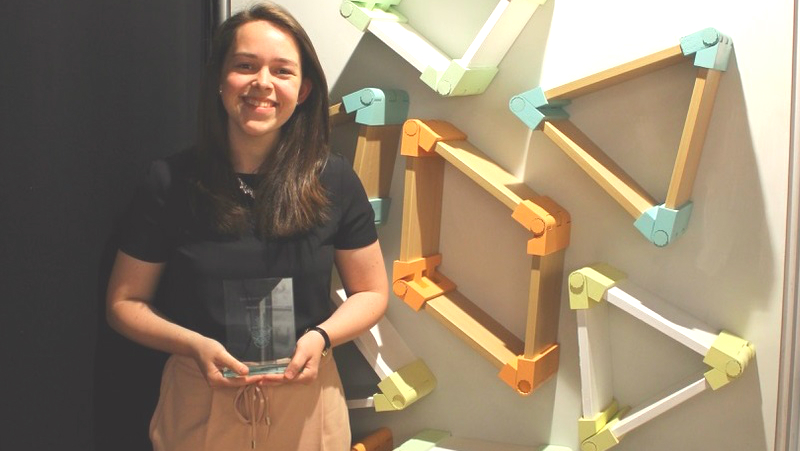 Graduate Alice dixon displaying her furniture and award