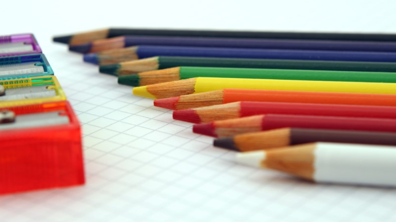 Colouring pencils lined up in rainbow order with corresponding rainbow coloured sharpeners