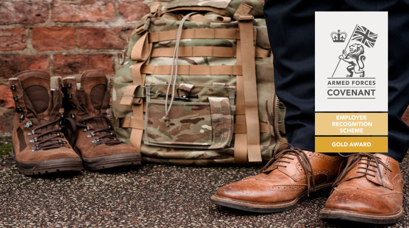 Army boots and rucksack alongside a man's legs and feet in suit trousers and smart shoes