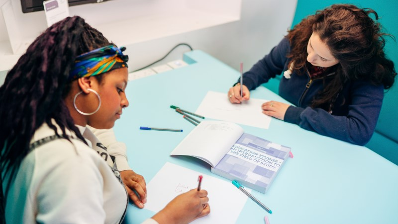 2 female students working at opposite sides of a light blue desk