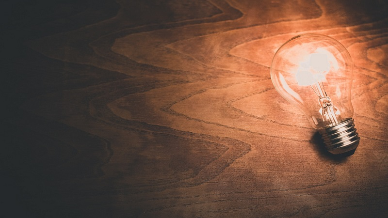 A lightbulb on a wooden desk