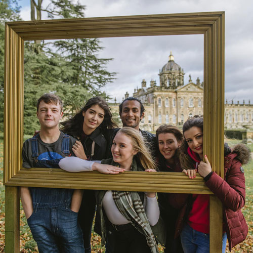 Group of happy students taking a picture at Castle Howard