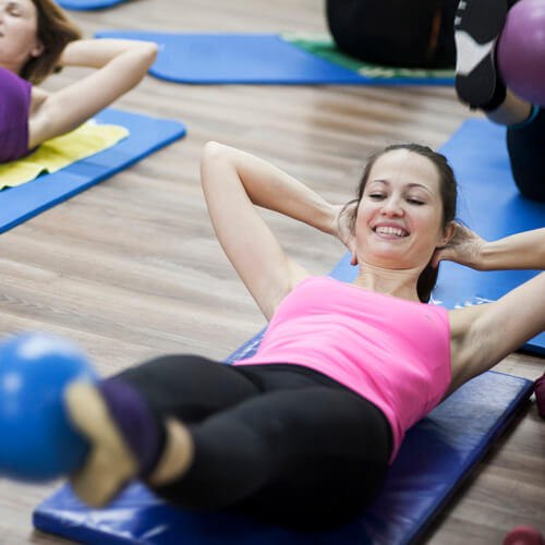 Lifting ball with legs during pilates class