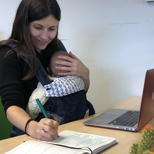 Woman holding baby and working at laptop on desk