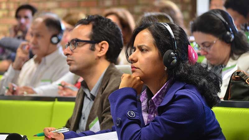 A woman and a man sitting listening. The woman has translation headphones on